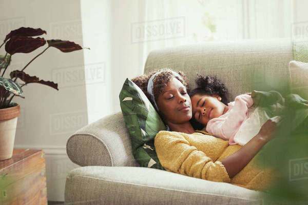 Serene mother and daughter napping and cuddling on sofa Royalty-free stock photo