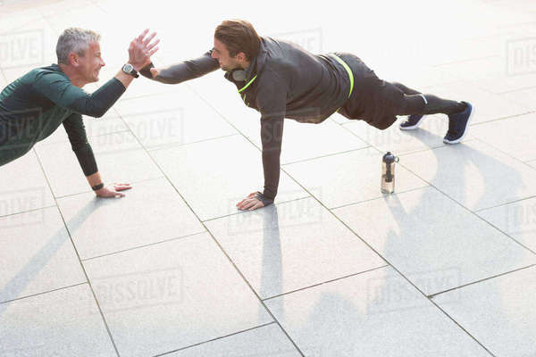 Men doing plank exercises and high-fiving Royalty-free stock photo