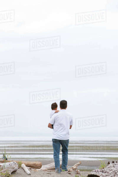 Father holding on on overcast beach Royalty-free stock photo