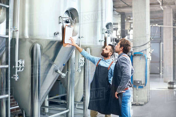 Male brewers checking clipboard on vat Royalty-free stock photo