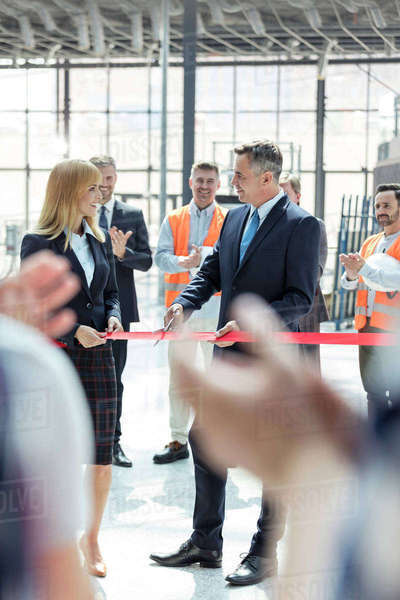 Business people cutting ribbon at new construction site ceremony Royalty-free stock photo