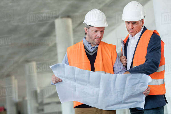 Male engineers examining underground blueprints at construction site Royalty-free stock photo
