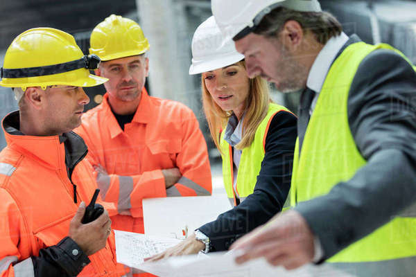 Engineers and construction workers reviewing blueprints at construction site Royalty-free stock photo