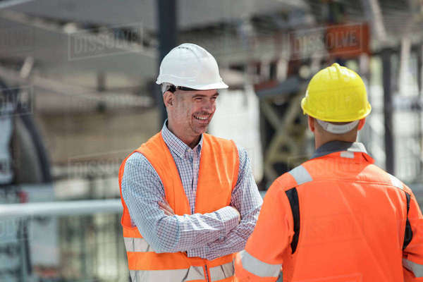 Smiling foreman talking to construction worker at construction site Royalty-free stock photo