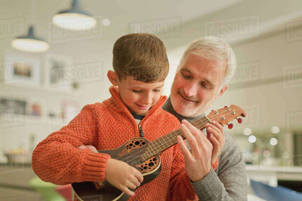 Father teaching son to play the ukulele Royalty-free stock photo