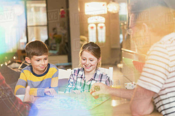 Father and children playing board game at table Royalty-free stock photo