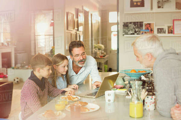 Male gay parents and children using laptop at breakfast kitchen counter Royalty-free stock photo