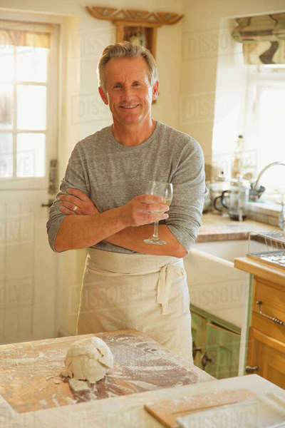 Portrait smiling senior man drinking wine and baking in kitchen Royalty-free stock photo