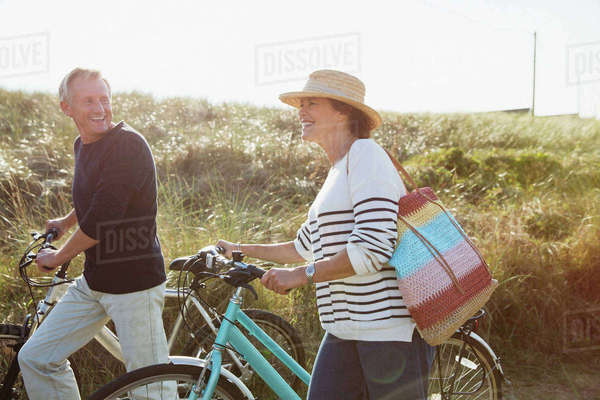 Mature couple walking bicycles on sunny beach grass path Royalty-free stock photo