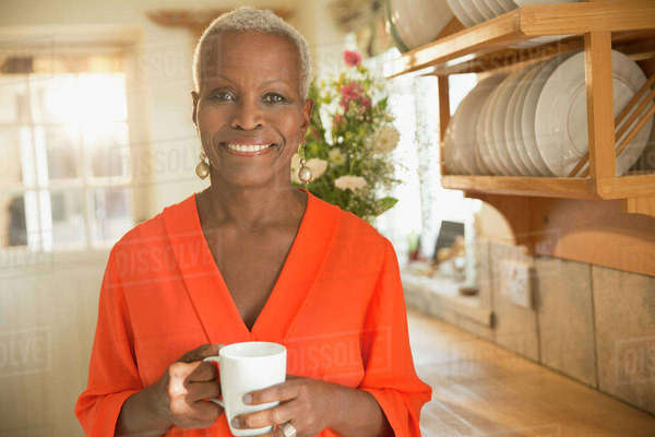 Portrait smiling senior woman drinking coffee in kitchen Royalty-free stock photo