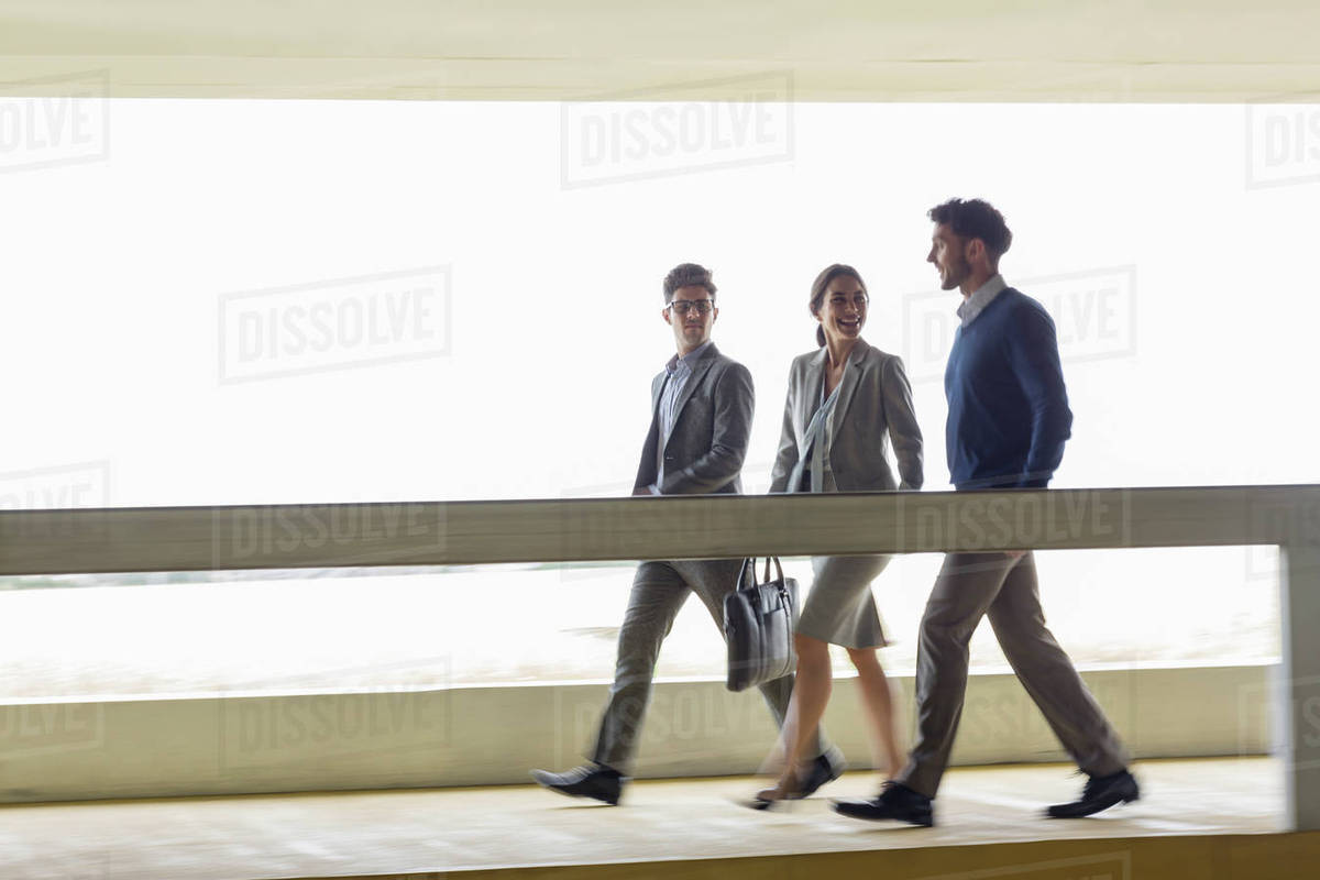 business people walking and talking along walkway stock photo