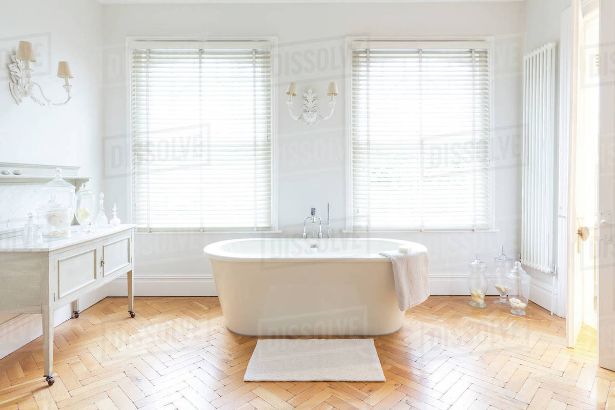 White, luxury home showcase bathroom with soaking tub and parquet ...