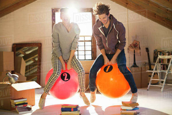 Couple jumping on exercise balls together Royalty-free stock photo