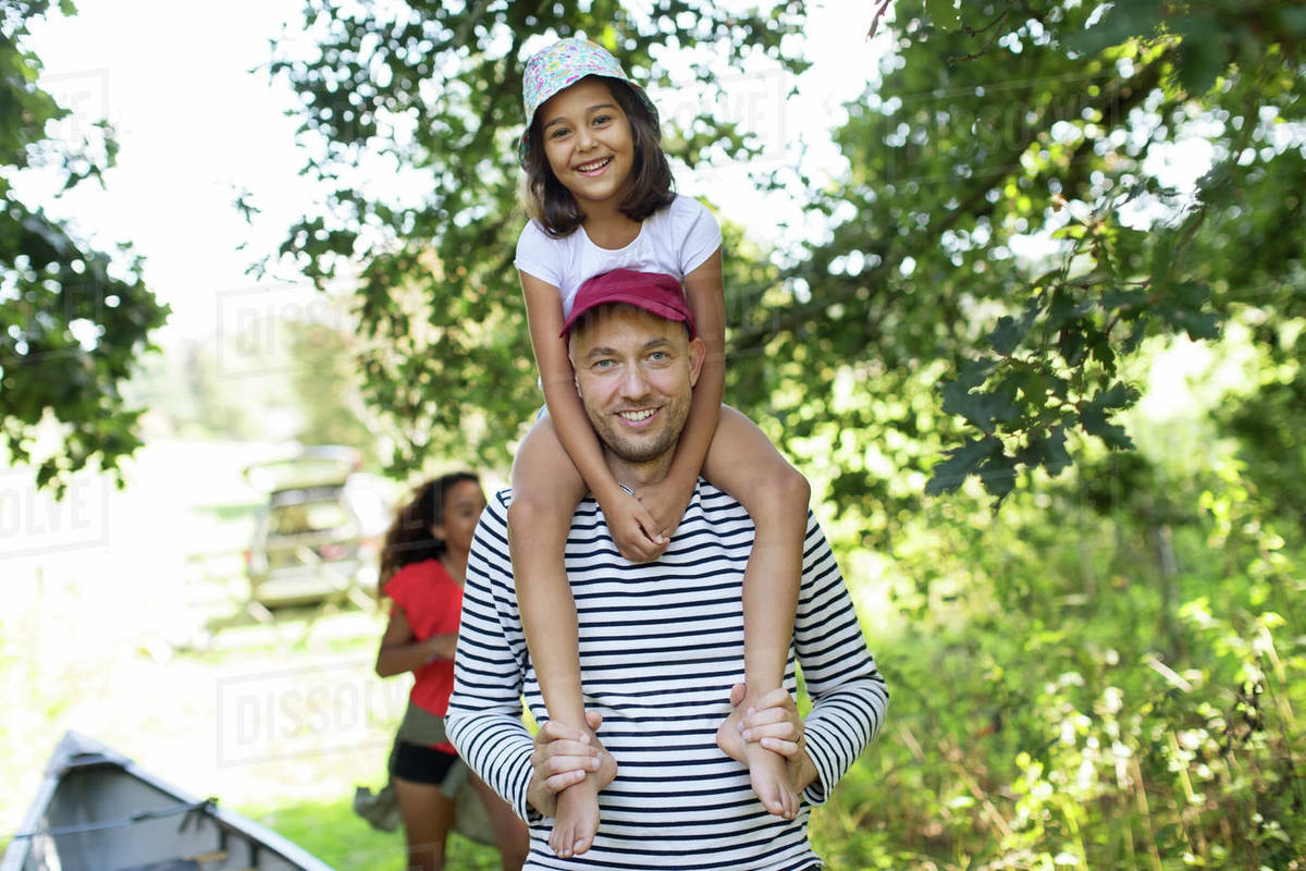 Portrait father carrying daughter on shoulders in woods Royalty-free stock photo