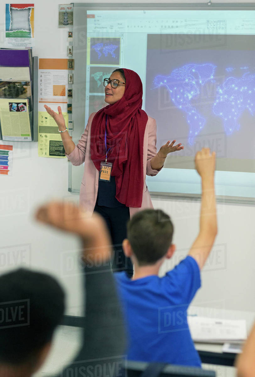 Female teacher in hijab leading lesson at projection screen in classroom Royalty-free stock photo