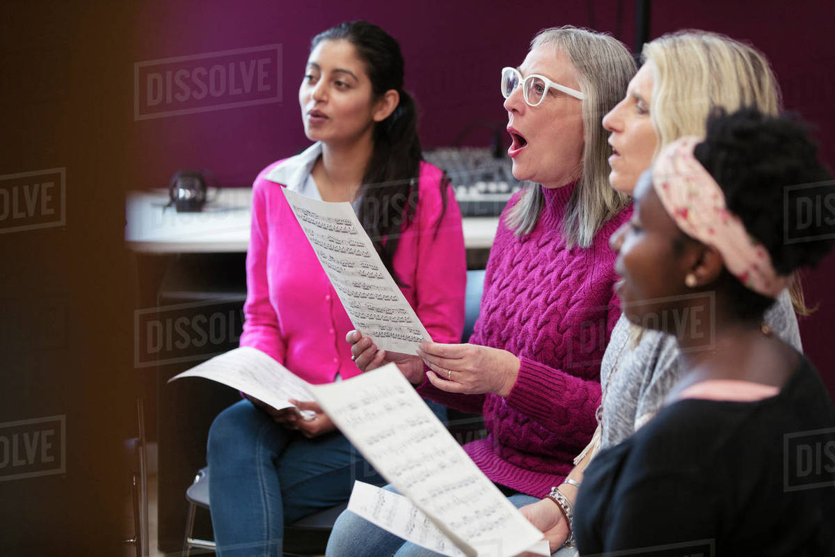 Womens choir with sheet music singing in music recording studio Royalty-free stock photo