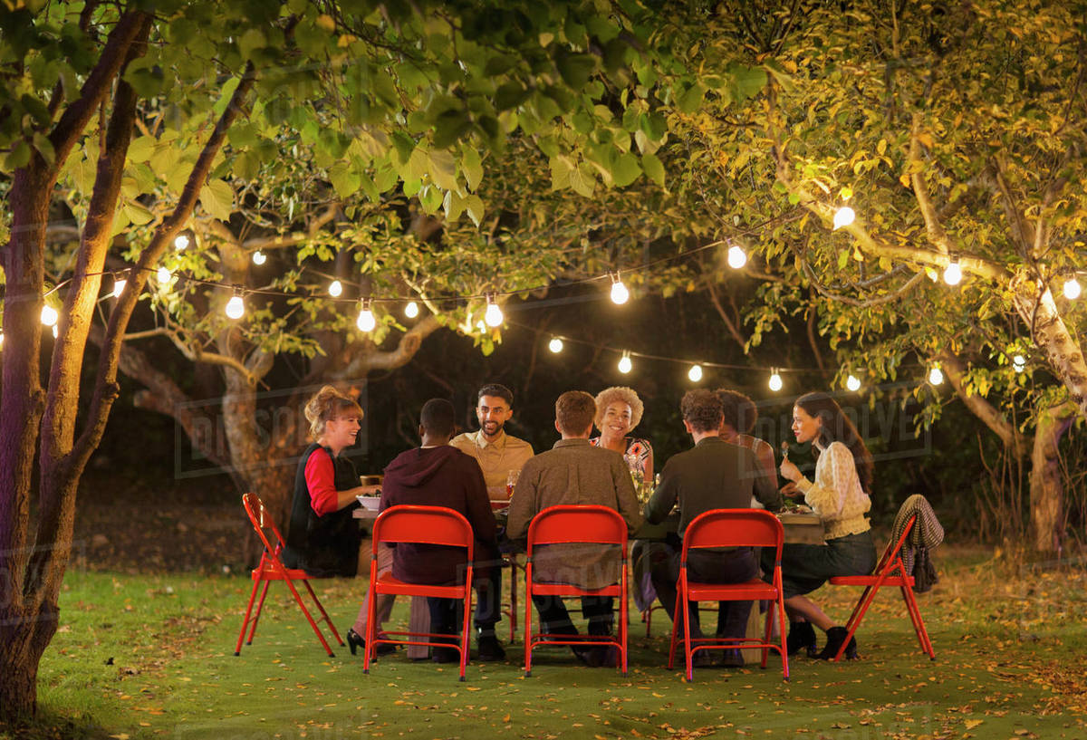 new product 00851 ca4e0 Friends enjoying dinner garden party under trees with fairy lights stock  photo