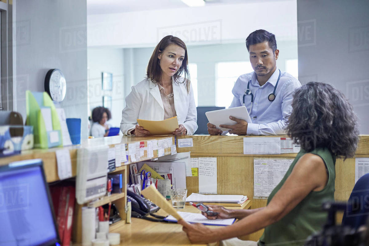 Doctors and receptionist talking in clinic Royalty-free stock photo