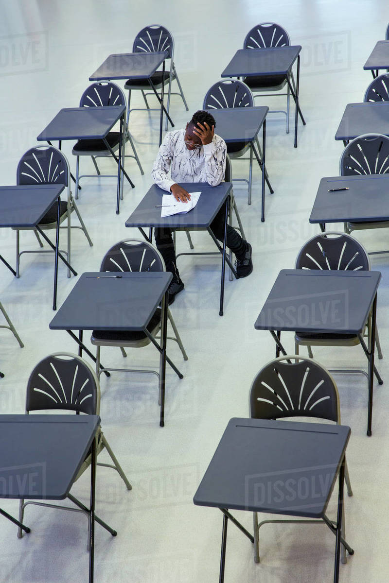 Dedicated high school boy student taking exam at desk in classroom Royalty-free stock photo