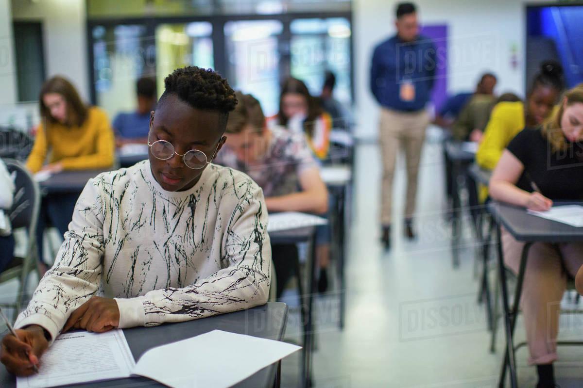 Focused high school boy student taking exam at desk Royalty-free stock photo