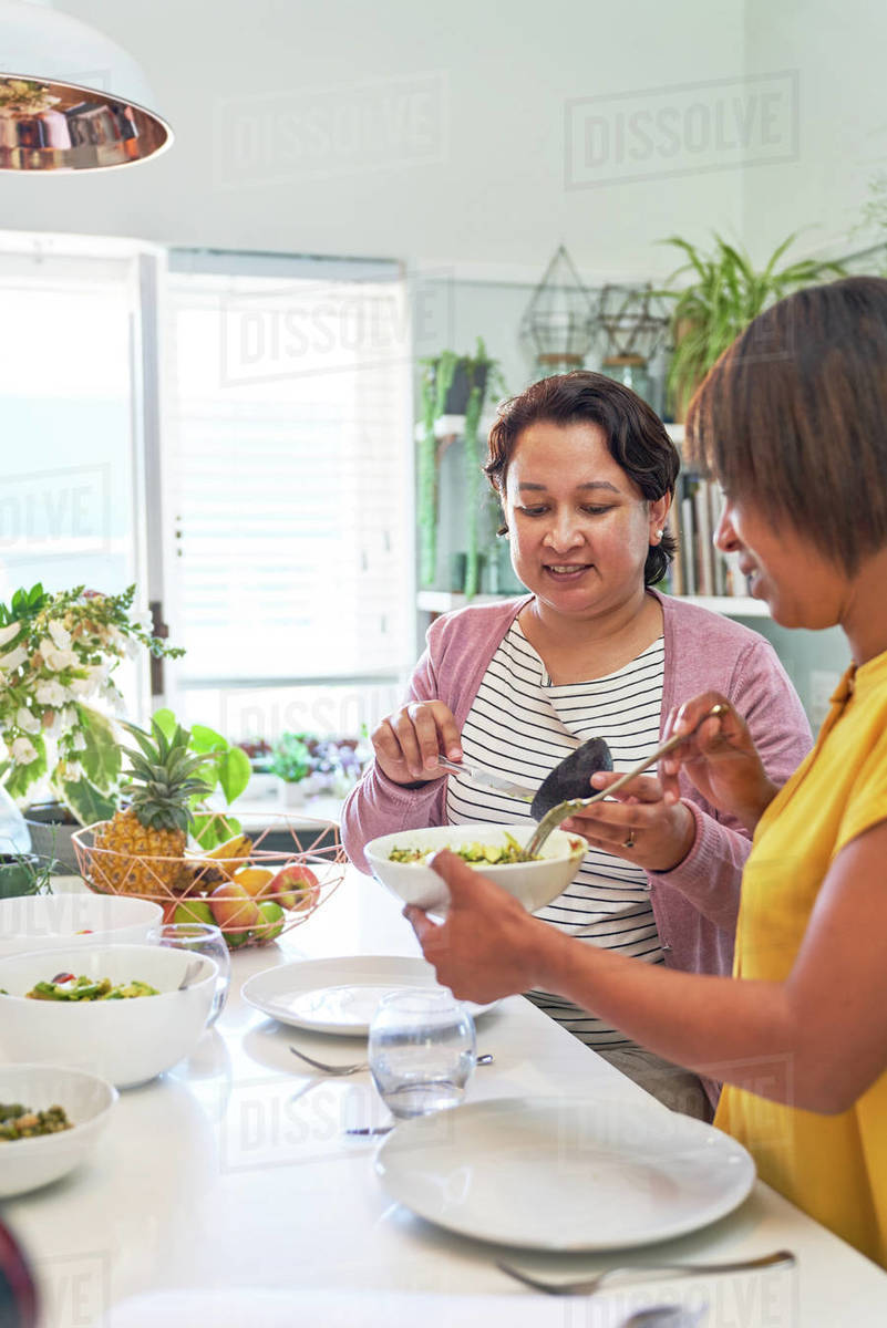 Women friends eating salad at kitchen island Royalty-free stock photo