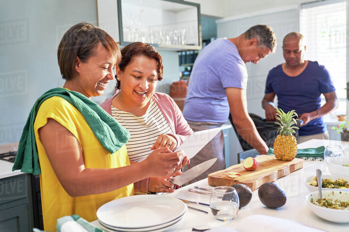 Happy couple friends using digital tablet and cooking in kitchen Royalty-free stock photo