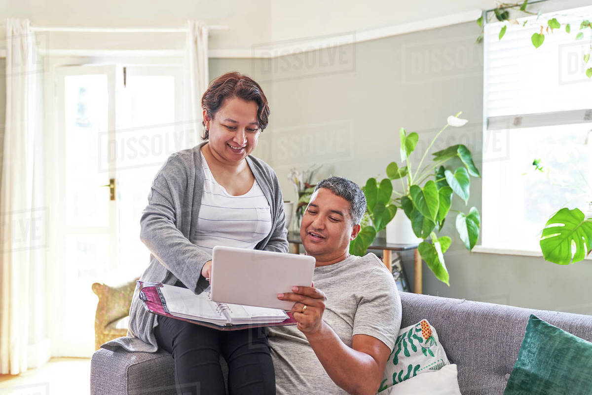 Mature couple using digital tablet on living room sofa Royalty-free stock photo