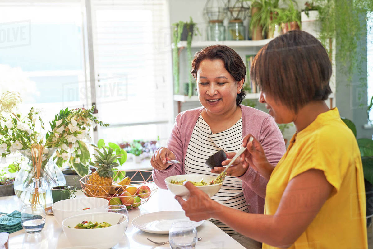 Women friends eating salad in kitchen Royalty-free stock photo