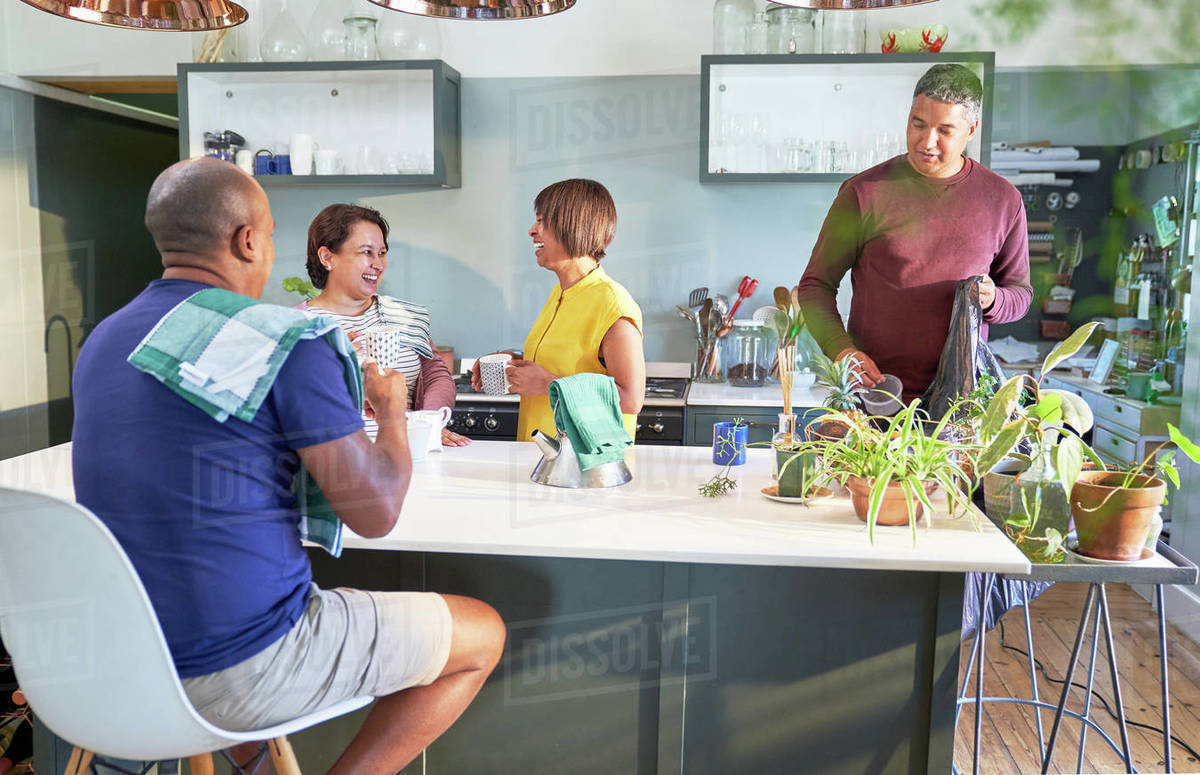 Mature couple friends talking and drinking tea in kitchen Royalty-free stock photo