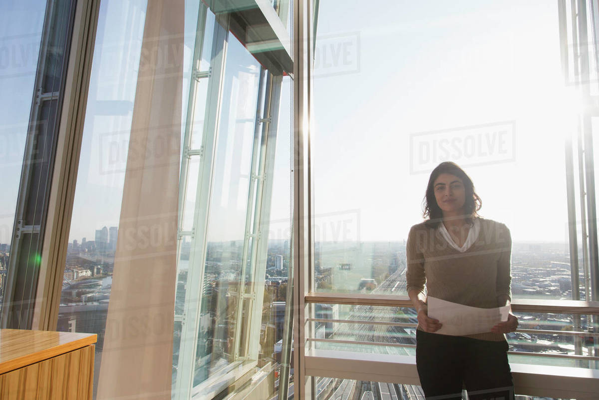 Portrait confident businesswoman at sunny highrise office window Royalty-free stock photo