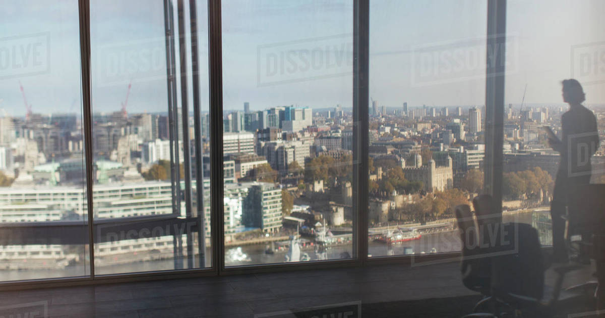 Silhouette businessman at highrise window overlooking city, London, UK Royalty-free stock photo
