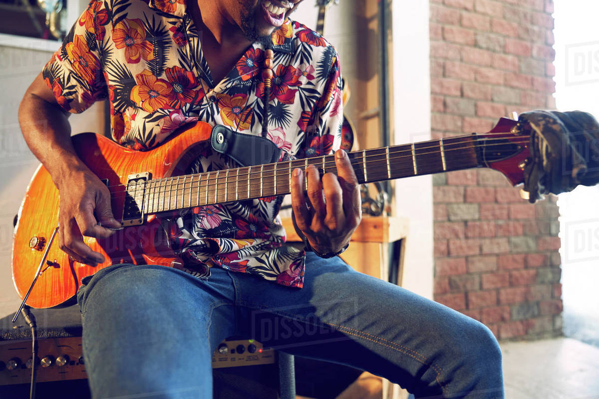 Male musician playing electric guitar in garage Royalty-free stock photo