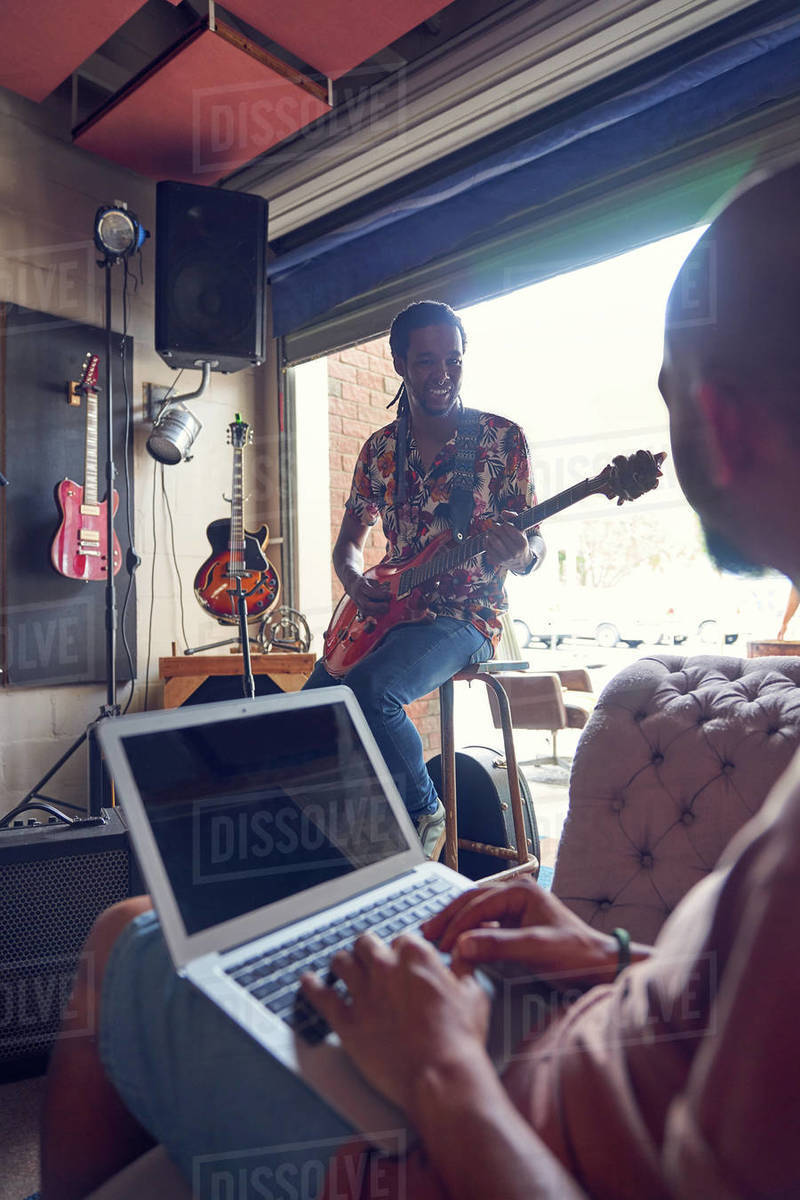 Musicians with laptop and electric guitar in garage recording studio Royalty-free stock photo