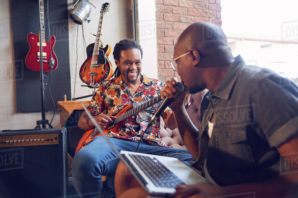 Happy male musicians practicing in recording studio Royalty-free stock photo