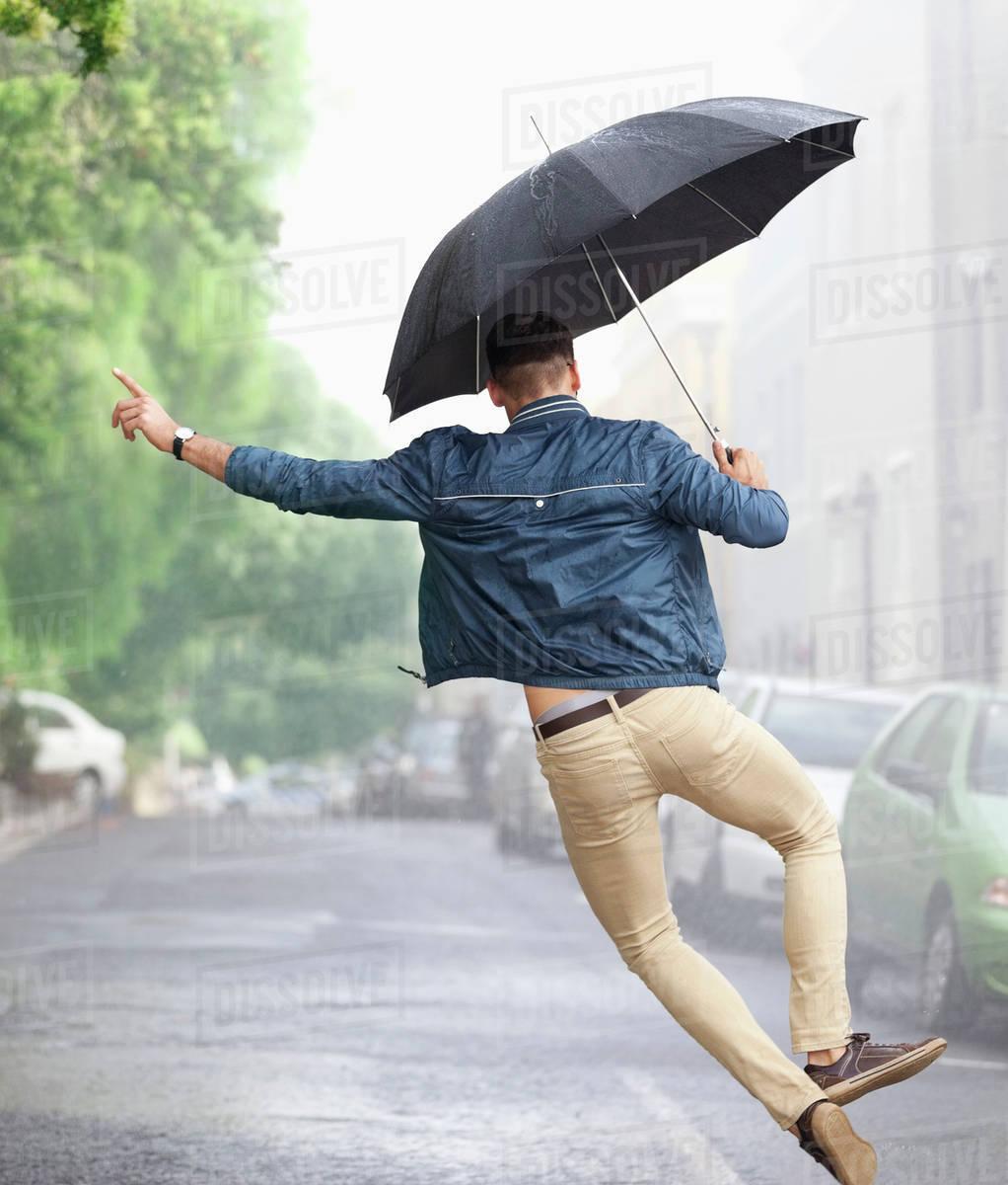 man dancing with umbrella in rainy street stock photo dissolve