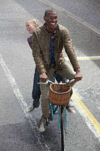 Happy couple riding bicycle in rainy street Royalty-free stock photo