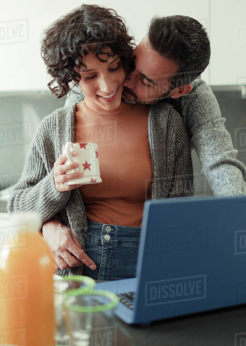 Husband kissing wife working from home at laptop in kitchen Royalty-free stock photo