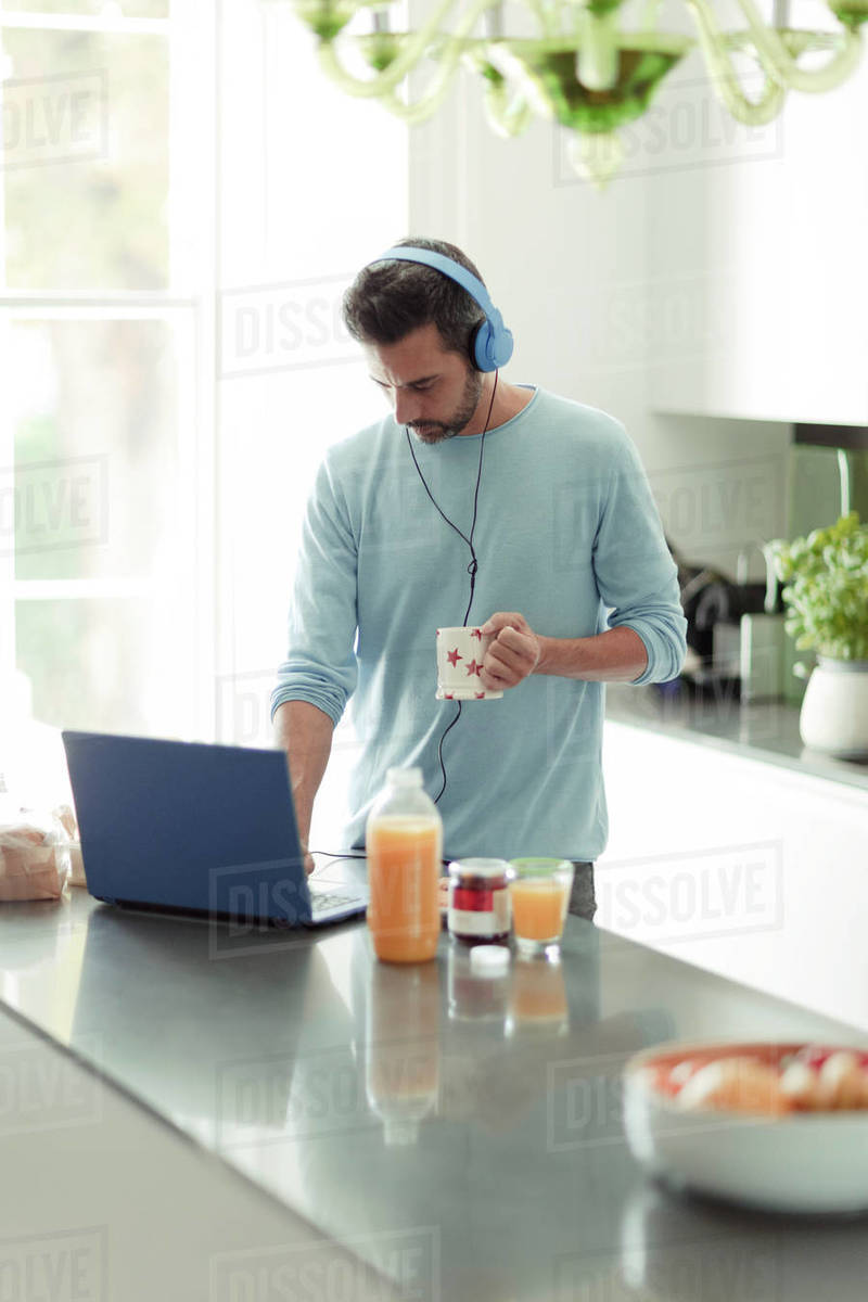 Man with headphones working from home at laptop in morning kitchen Royalty-free stock photo