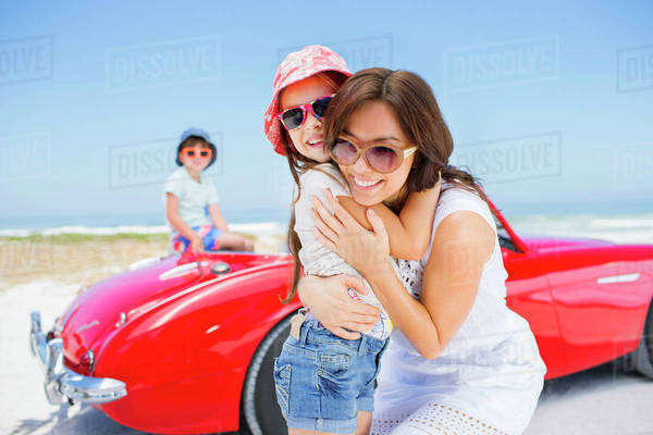 Mother and daughter hugging by convertible at beach Royalty-free stock photo