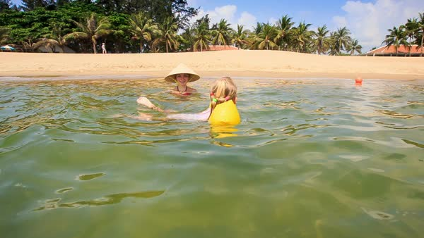 6674a5d607 Little girl in yellow safety armbands swims from mother in hat to  transparent sea against sandy