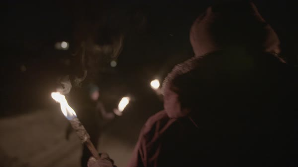 Tracking shot of people walking on a snowy road with burning torches Royalty-free stock video
