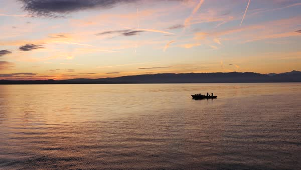 Aerial shot of silhouetted fishermen fishing from a boat on a lake Royalty-free stock video