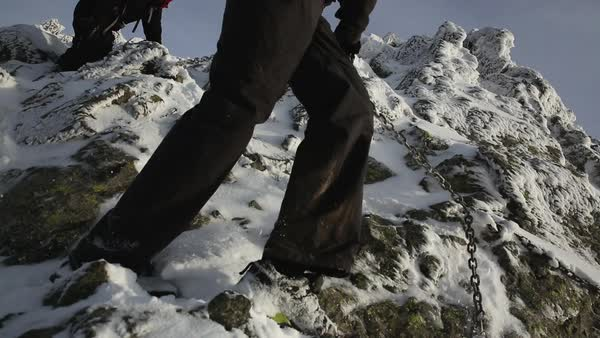 Hand-held shot of hikers climbing on snowy rocks with help of a chain Royalty-free stock video
