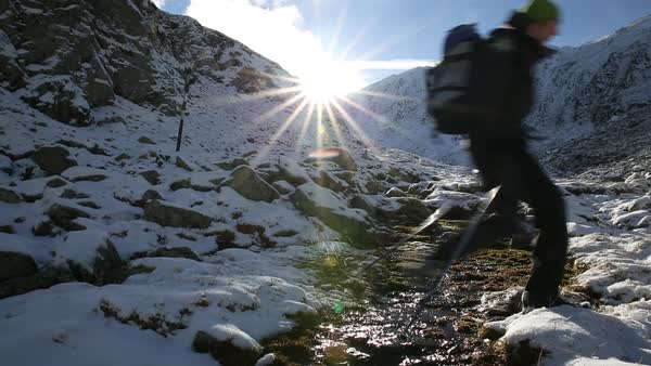 Hand-held shot of two hikers jumping over a creek in Fagaras Mountains Royalty-free stock video