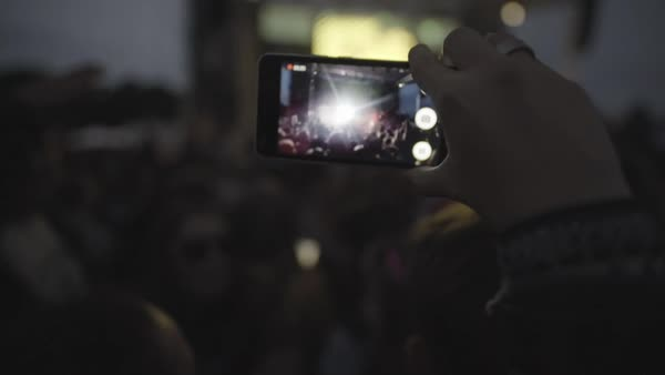 Hand-held shot of a woman filming a concert with her smartphone Royalty-free stock video