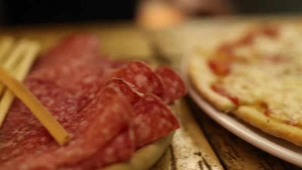 Panning shot of served olives and salami and pizza Royalty-free stock video