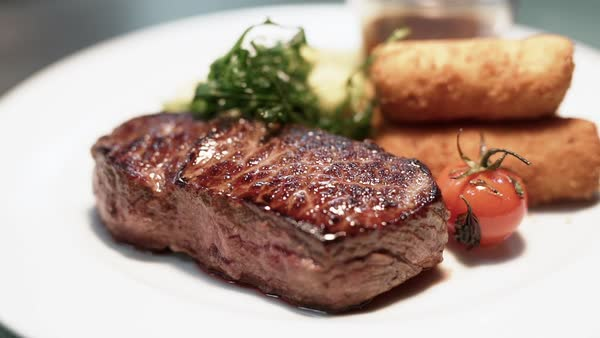 Close-up shot of a rump steak with vegetables and croquettes Royalty-free stock video