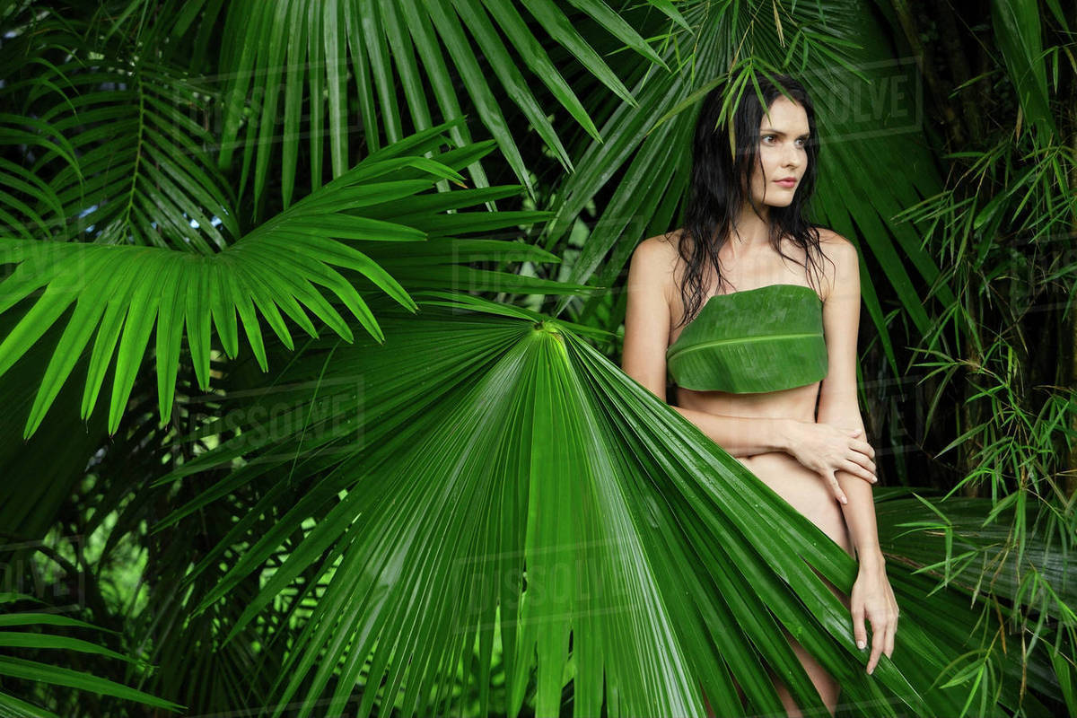 Naked woman behind big tropical leaves - Stock Photo