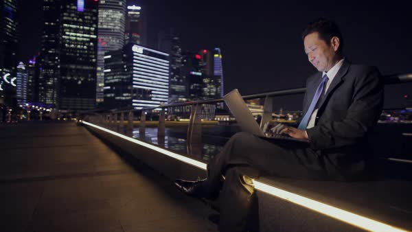 Businessman Sitting on Bench Working on Laptop with City Scape in Background at Night / Singapore Royalty-free stock video