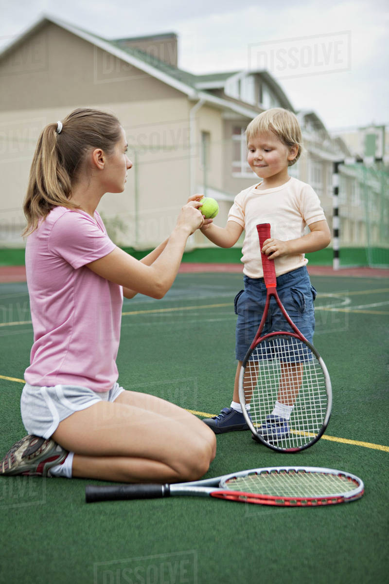 A mother teaching her young son tennis - Stock Photo - Dissolve